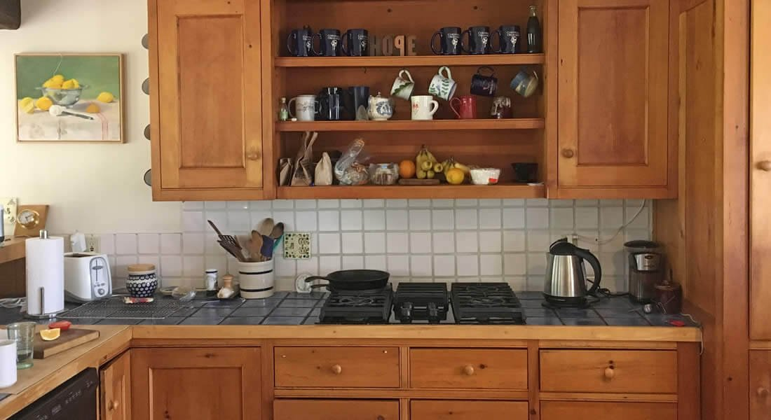 Rustic wood kitchen cabinets with blue tiled tops, gas cooktop, white tiled backsplash, open shelves with assorted mugs and snacks
