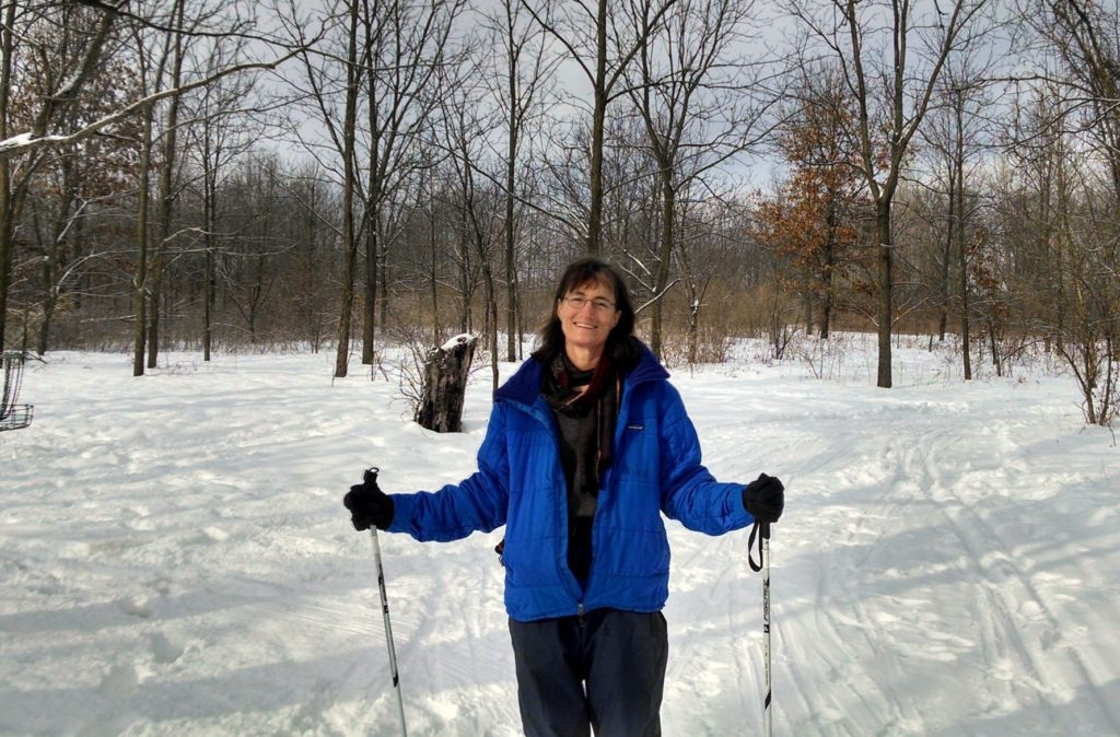 Woman in a blue snow jacket standing in the snowy woods with ski polls