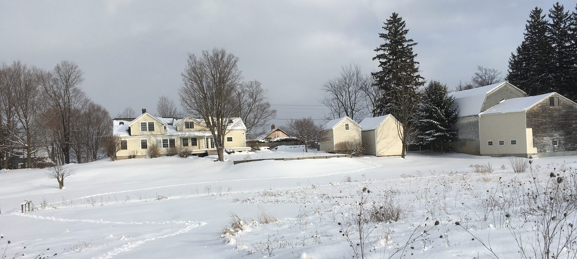 View of the yellow house and outbuildings, and a gray barn in the snow in the distance.