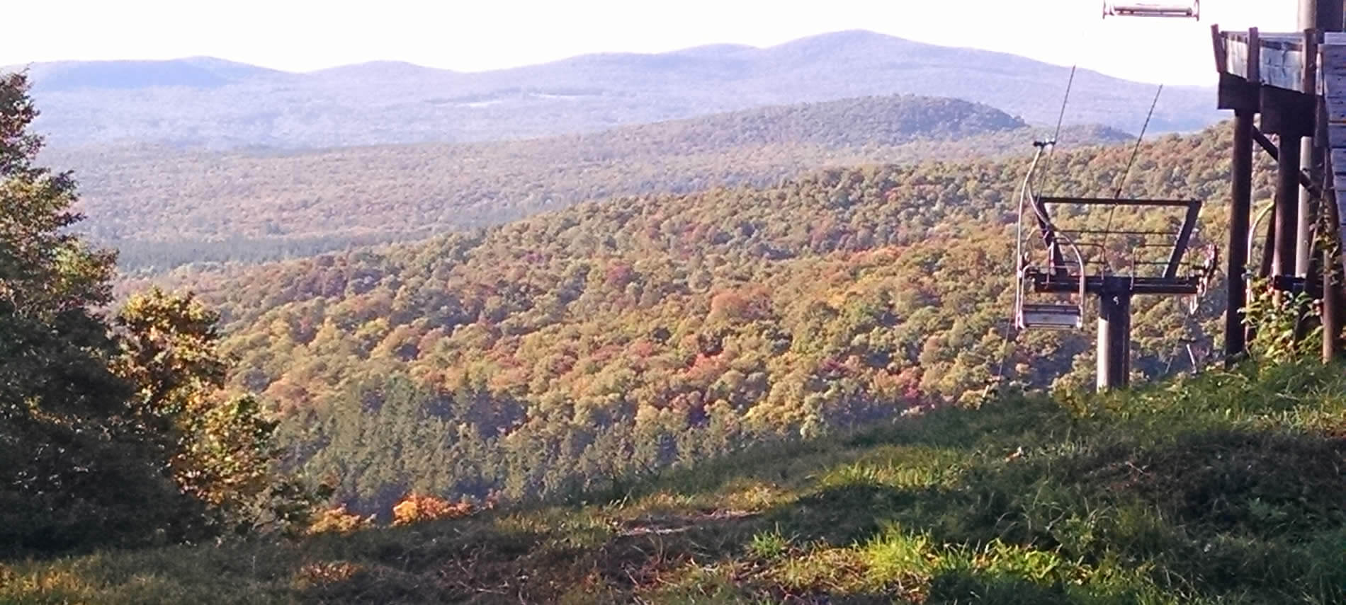 Distant rolling hills and mountains in the autumn covered in shades of yellow, green and red
