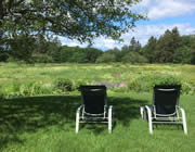 Backside of two black and white chairs in sun-dappled grass overlooking a green field with trees in the distance