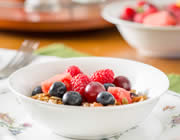 Close-up view of white bowl of granola with blue and red berries