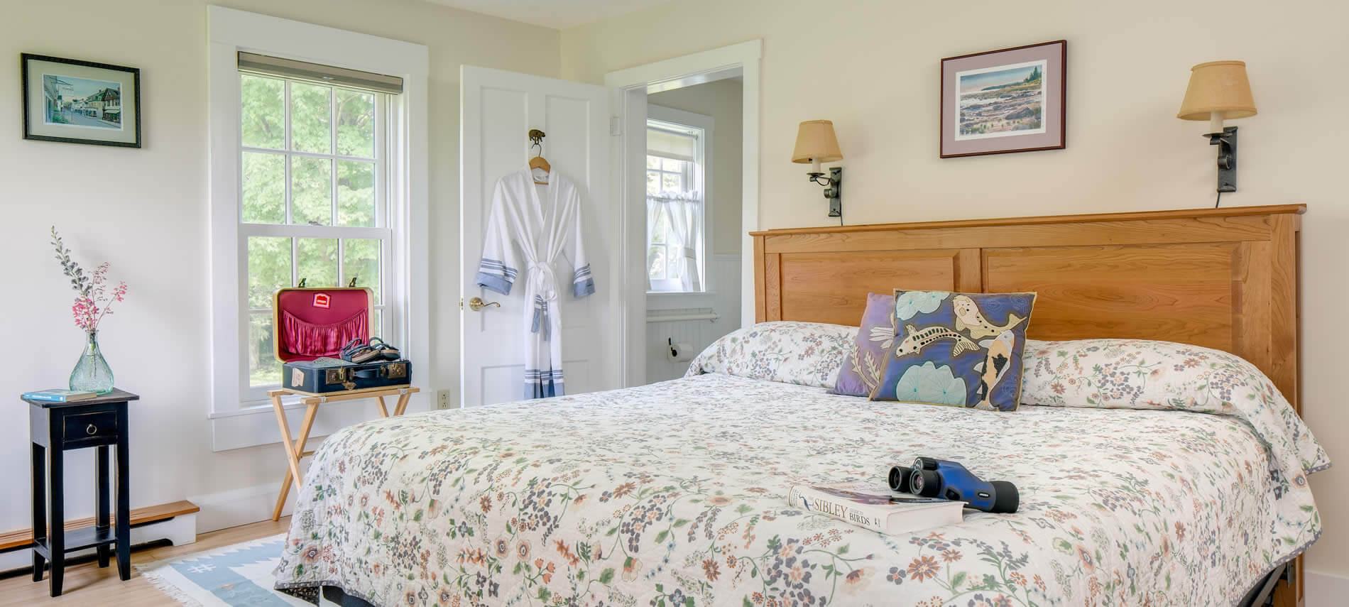 Bright beige room with trim and doors, wood floor, and two sconce lights over a wood bed with floral bedspread