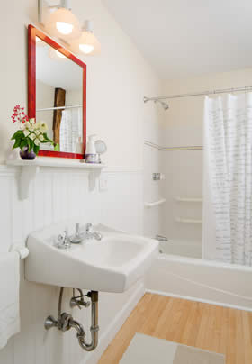 Bathroom with beige walls, white tub and sink, wood floors and red wood vanity mirror with white shelf