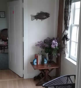Corner of room with light wood flooring, white walls, and a wood table with lilacs in front of a window