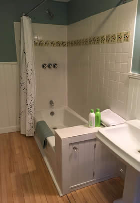 Bathroom with white tiled tub shower, white beadboard and blueish green walls, wood floors and white pedestal sink