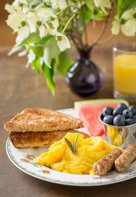 Table with plate of scrambled eggs, sausage, toast, watermelon and blueberries, glass of orange juice and vase of white flowers