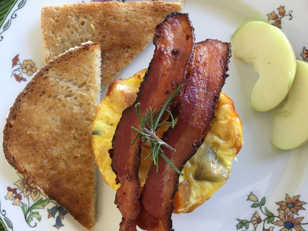 Two strips of bacon laid across egg strata with toast and apple slices on a white china plate.